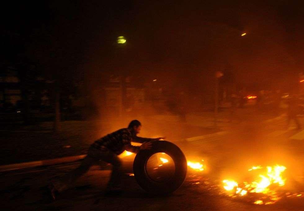 Un piquete coloca un neumático en una barricada puesta en Mercabarna, Barcelona.